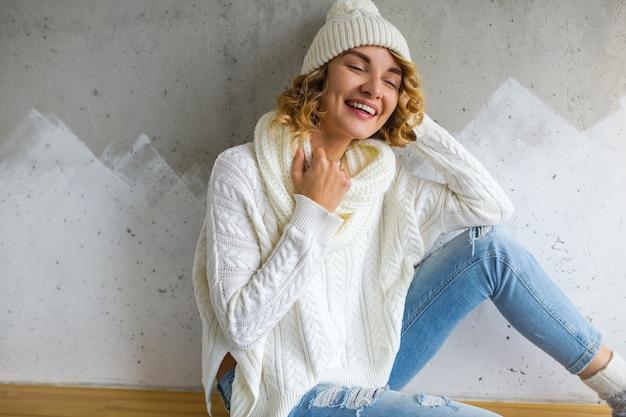 Mooie jonge vrouwenzitting tegen muur die witte sweater en spijkerbroek, gebreide muts en sjaal draagt