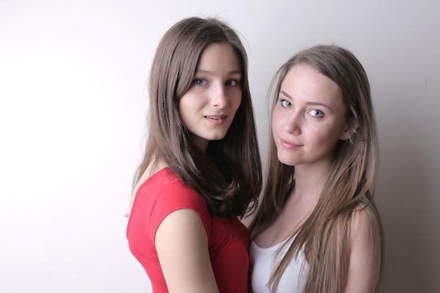 Mooie jonge vrouwtjes die zich tegen een witte muur bevinden