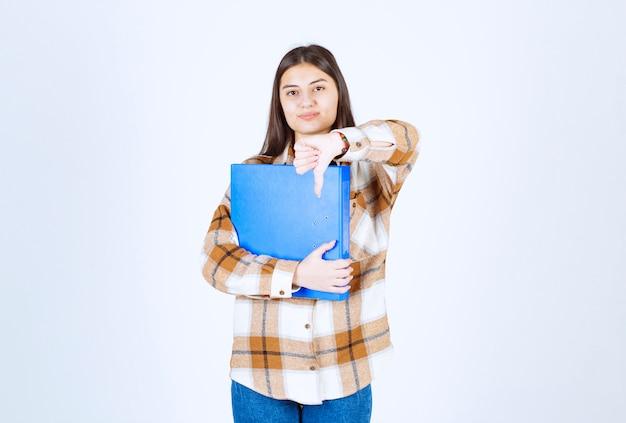 Mooie jonge werknemer met blauwe map duimen naar beneden geven.