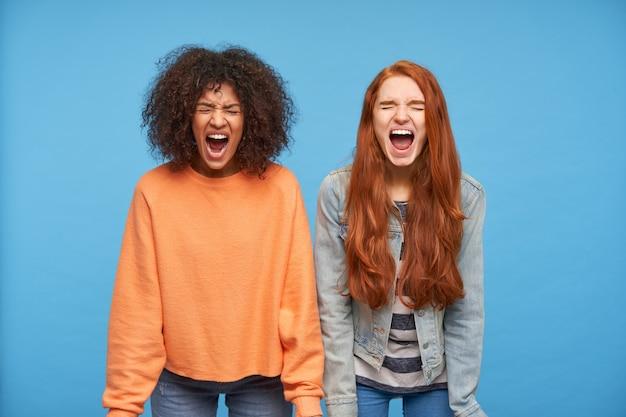 Mooie jonge woedende dames die hun ogen gesloten hielden terwijl ze verhit schreeuwden met wijd opengesperde monden terwijl ze over de blauwe muur stonden