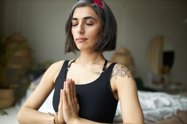Mooie jonge womanwith grijsachtig haar, tatoeage op schouder en neusring die handen samen in namaste bij hartchakra drukken