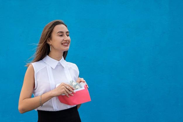 Mooie jonge zakendame met een envelop met dollars op een blauwe achtergrond. concept van corruptie, salaris in een envelop of winkelen