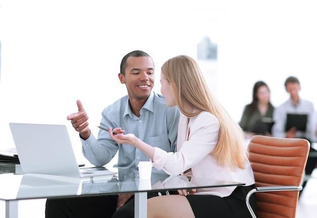 Mooie jonge zakenpartners gebruiken een laptop en bespreken documenten.foto met kopieerruimte