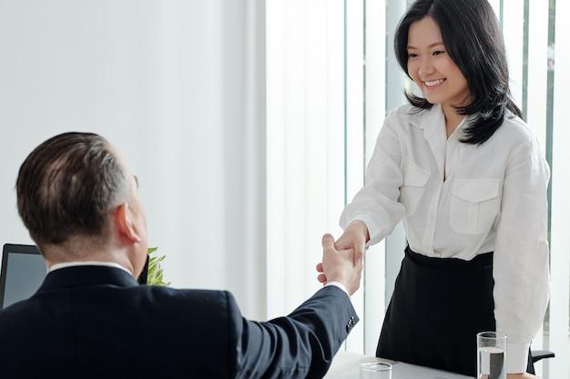 Mooie jonge zakenvrouw die de hand schudt van het afdelingshoofd voor een vergadering of sollicitatiegesprek