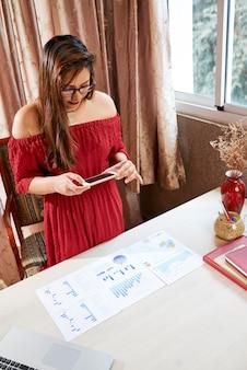 Mooie jonge zakenvrouw die gedrukte grafieken op haar tafel fotografeert om bestanden naar collega's te sturen met behulp van messenger