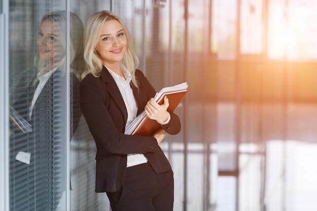 Mooie jonge zakenvrouw glimlachend en permanent met map op kantoor. camera kijken. kopieer ruimte