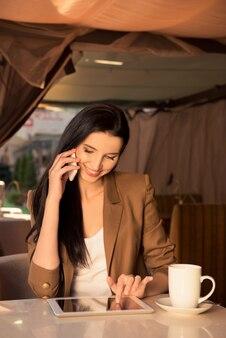 Mooie jonge zakenvrouw in een café praten aan de telefoon met tablet