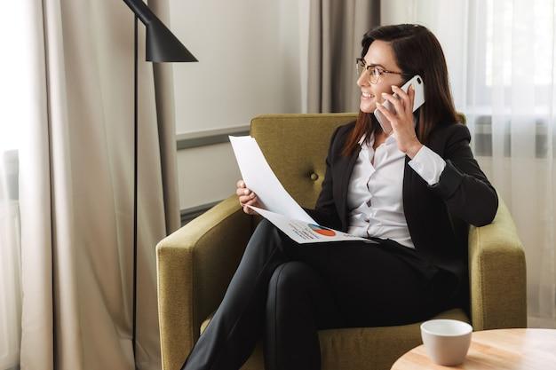 Mooie jonge zakenvrouw in formele kleding binnenshuis thuis praten via de mobiele telefoon werken met documenten.