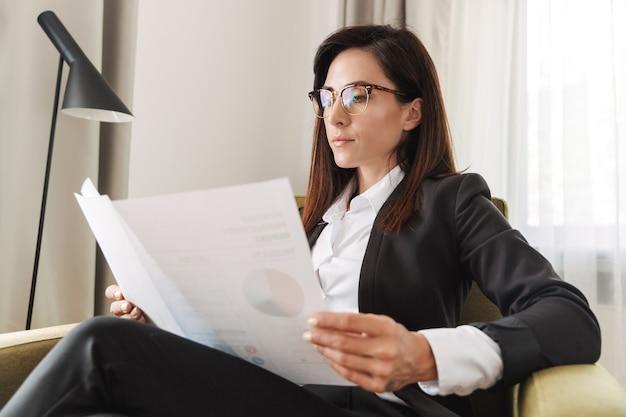 Mooie jonge zakenvrouw in formele kleding binnenshuis thuis werken met documenten en afbeeldingen.