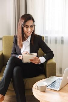 Mooie jonge zakenvrouw in formele kleding binnenshuis thuis werken met laptopcomputer schrijven van notities.