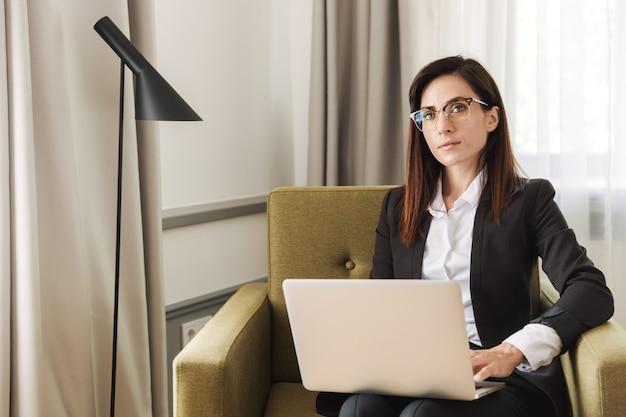 Mooie jonge zakenvrouw in formele kleding binnenshuis thuis werken met laptopcomputer.