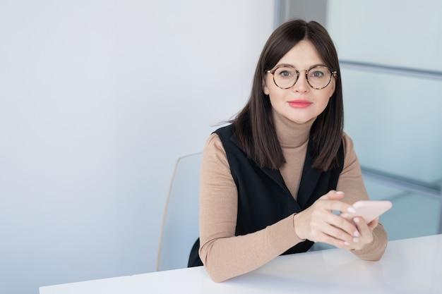 Mooie jonge zakenvrouw in smart casual en bril met behulp van smartphone zittend door bureau tegen witte muur in kantoor