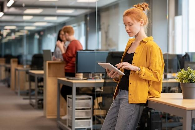 Mooie jonge zakenvrouw in vrijetijdskleding presentatie maken in digitale tablet terwijl leunend op bureau met groene plant in bloempot