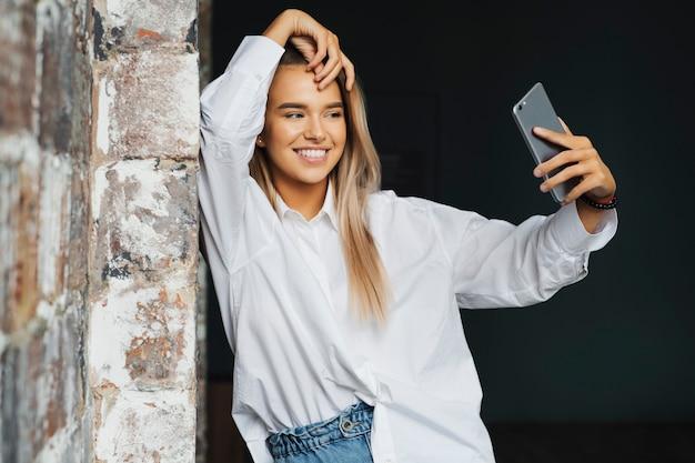 Mooie jonge zakenvrouw in wit overhemd staat in de buurt van bakstenen muur