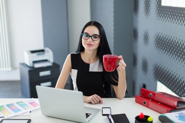 Mooie jonge zakenvrouw in zwarte jurk en bril zitten aan de tafel en werken met koffie in de hand