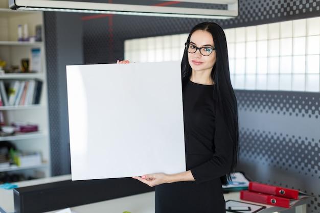 Mooie jonge zakenvrouw in zwarte jurk en glazen houden lege poster