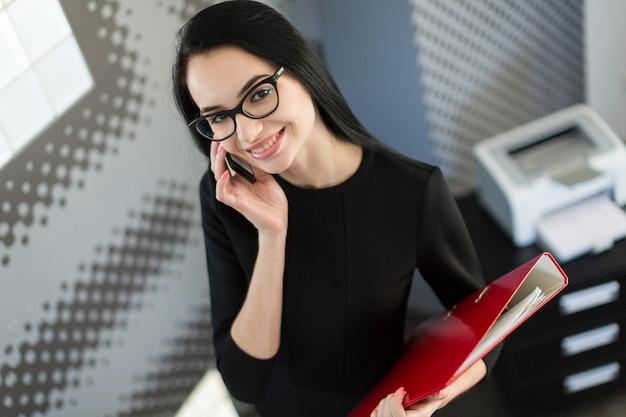 Mooie jonge zakenvrouw in zwarte jurk en glazen houden papieren map