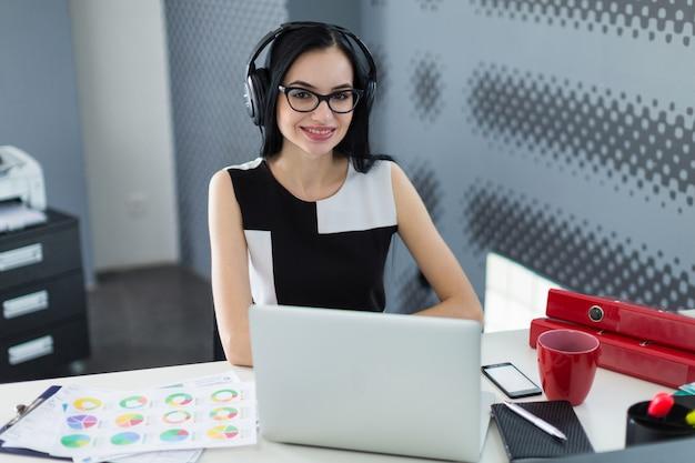 Mooie jonge zakenvrouw in zwarte jurk, koptelefoon en bril zitten aan de tafel en werken op laptop