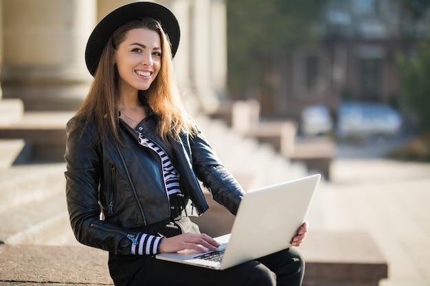 Mooie jonge zakenvrouw meisje werkt met de laptop van haar merk in het stadscentrum
