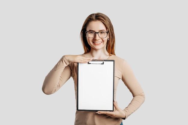 Mooie jonge zakenvrouw met een bril houdt een klembord met mock-up lege ruimte geïsoleerd op een grijze achtergrond. het bereiken van het bedrijfsconcept van de carrièrerijkdom. cover voor online leren