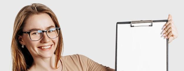 Mooie jonge zakenvrouw met een bril houdt een klembord met mock-up lege ruimte geïsoleerd op een grijze achtergrond. het bereiken van het bedrijfsconcept van de carrièrerijkdom. omslag online leren