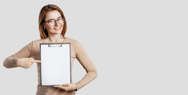 Mooie jonge zakenvrouw met een bril houdt een klembord vast met een mock-up lege ruimte geïsoleerd op een grijs oppervlak gray
