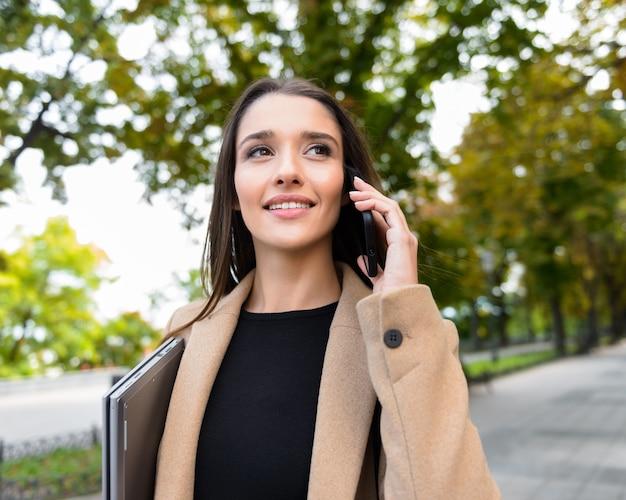 Mooie jonge zakenvrouw met een herfstjas die buiten in het park loopt, een laptop draagt, praat op een mobiele telefoon