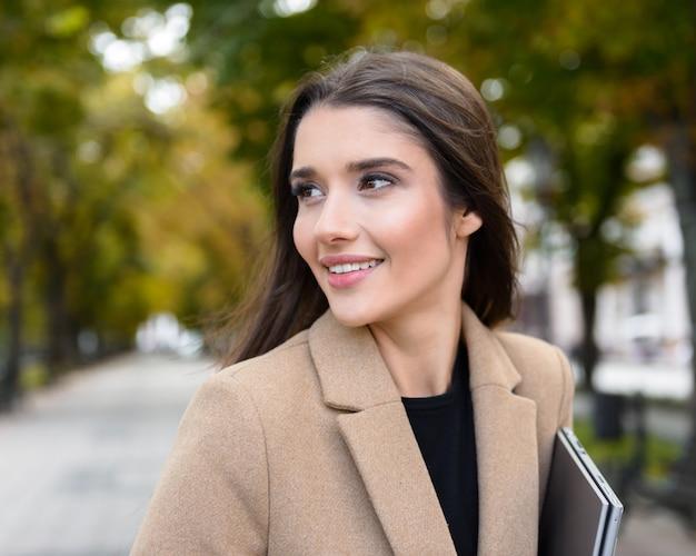 Mooie jonge zakenvrouw met een herfstjas die buiten in het park loopt en een laptop draagt