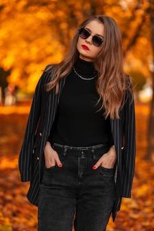 Mooie jonge zakenvrouw met zonnebril in een stijlvol pak met een modieuze blazer loopt in een herfstpark met oranje bladeren