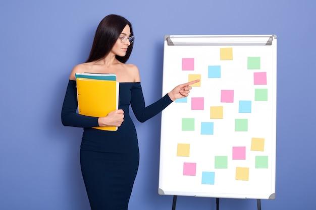 Mooie jonge zakenvrouw papieren map in handen houden, permanent in de buurt van flip-over met stickers