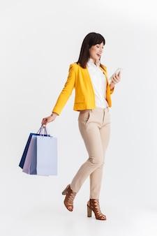 Mooie jonge zakenvrouw poseren geïsoleerd over witte muur met behulp van mobiele telefoon met boodschappentassen.