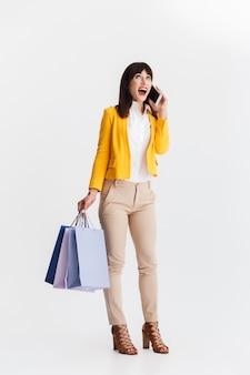 Mooie jonge zakenvrouw poseren geïsoleerd over witte muur praten via de mobiele telefoon met boodschappentassen.