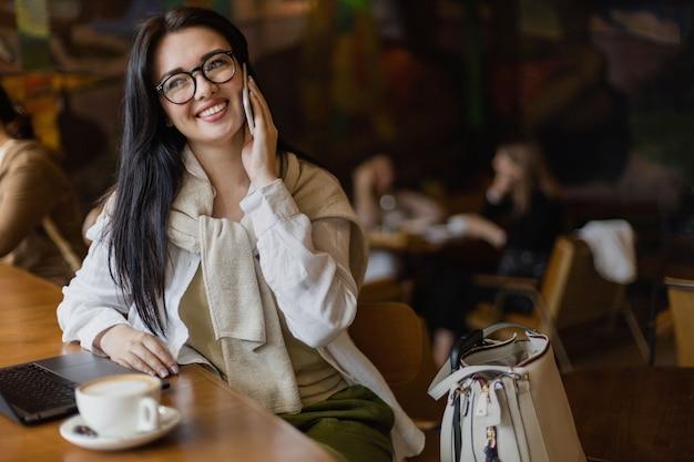 Mooie jonge zakenvrouw pratende smartphone zittend aan tafel in café met laptop en koffiekopje
