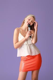 Mooie jonge zangeres met microfoon op paars