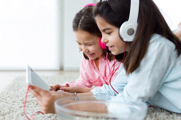Mooie jonge zussen luisteren naar muziek met digitale tablet a