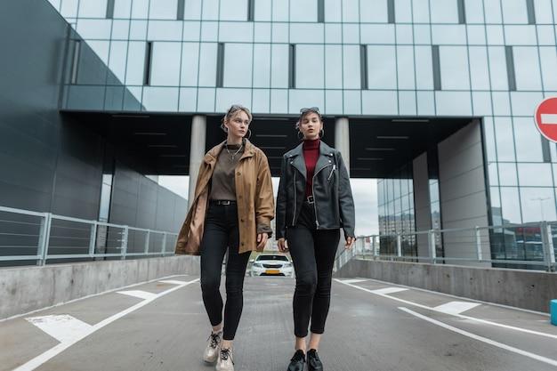 Mooie jonge zussen meisjes in een mode leren jas met stijlvolle zwarte jeans en schoenen lopen in de stad in de buurt van moderne gebouwen