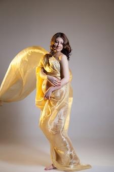 Mooie jonge zwangere brunette vrouw met gele transparante doek in studio opname geïsoleerd op een witte achtergrond. model staat met haar armen alsof ze de buik verbergt.