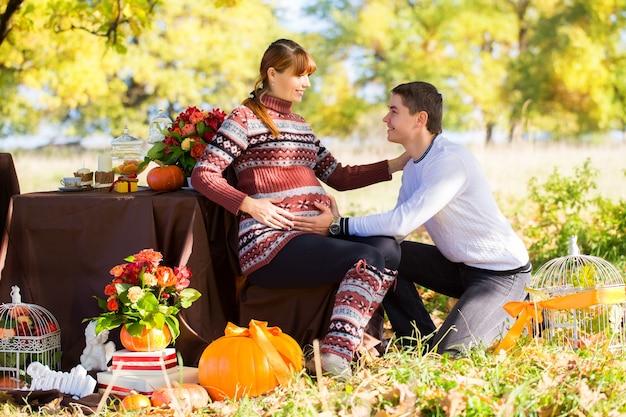 Mooie jonge zwangere paar met picknick in herfst park. gelukkige familie buiten. glimlachende man en vrouw ontspannen in het park. verhoudingen.