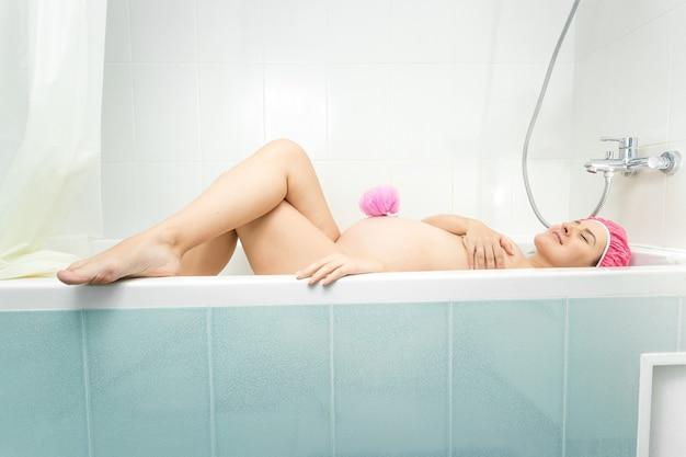 Mooie jonge zwangere vrouw die in bad ligt