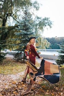 Mooie jonge zwangere vrouw in een rode jurk en stijlvolle hoed in het herfstpark jonge mooie dame w...