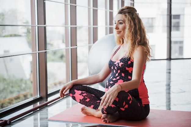 Mooie jonge zwangere vrouw mediteren in de hal.