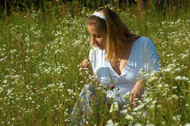 Mooie jonge zwangere vrouw met een blote buikzitting in bloemen bij weide.