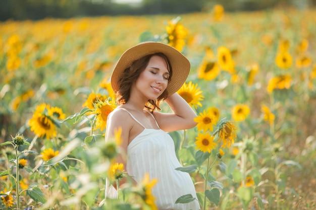 Mooie jonge zwangere vrouw op het zonnebloemgebied. portret van een jonge zwangere vrouw in de zon. zomer.