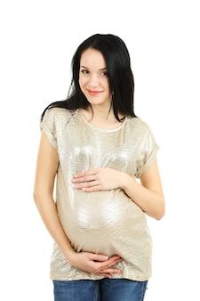 Mooie jonge zwangere vrouw wat betreft haar buik die op wit wordt geïsoleerd