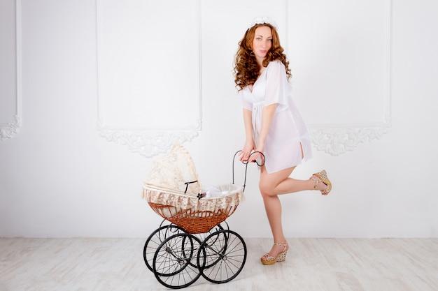 Mooie jonge zwangere vrouwentiener in witte kleding met kinderwagen