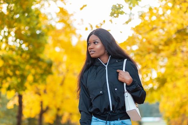 Mooie jonge zwarte afrikaanse vrouw in een modieus jasje met een handtas loopt in een herfstpark in canada met felgeel blad