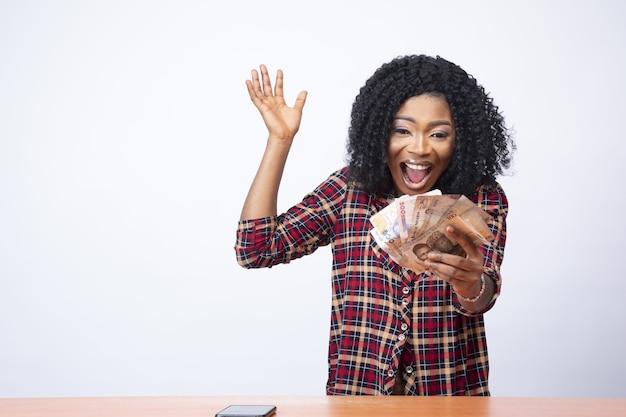 Mooie jonge zwarte dame geld houden en vieren voor een witte achtergrond