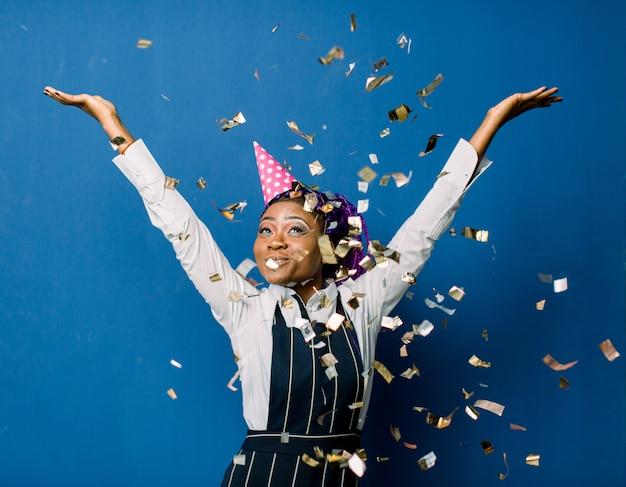 Mooie jonge zwarte die verjaardag of nieuw jaar en chrismaspartij vieren terwijl het blazen van confettiendecoraties aan camera die over blauwe ruimte wordt geïsoleerd