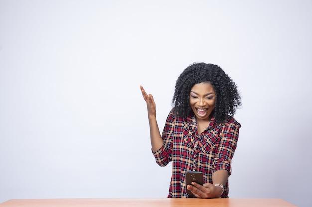 Mooie jonge zwarte vrouw die verrast kijkt en opgewonden voelt tijdens het gebruik van haar telefoon