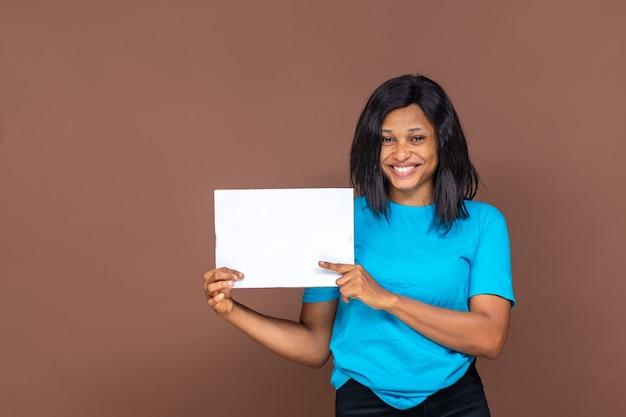Mooie jonge zwarte vrouw houdt een lege banner omhoog, ze is blij en heeft een glimlach op haar gezicht